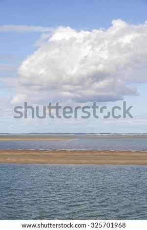 maritime seaside landscape with water, sand bank and white cloud, garonne estuary near Royan, France