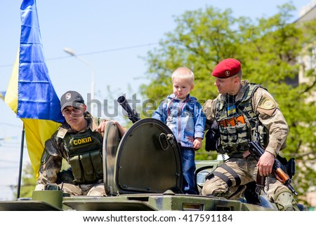 MARIUPOL MAY 9 : Events to commemorate the anniversary of the Victory in World War II. Children playing on military equipment, Child with a soldier. May 9 2016 Mariupol, Ukraine