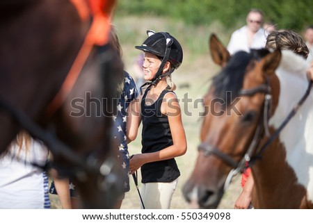 MARIUPOL,UKRAINE - 17 JULY,2015: Horse riding contest between young horsemen.Horseback riding competition outdoor in summer.Equitation challenge among women