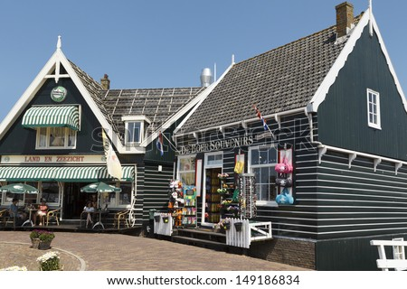 MARKEN - JULY 15: Typically Dutch wooden houses in Marken in the Netherlands house a bar and a souvenir shop, on July 15, 2013. - stock photo