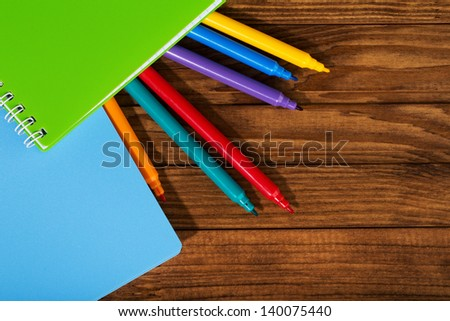marker and notebooks on a wooden table - stock photo