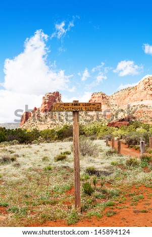 Marker for Big Park Loop and Courthouse Butte hiking trail in Sedona, Arizona with red rock mountains and a bright blue sky in the background. - stock photo