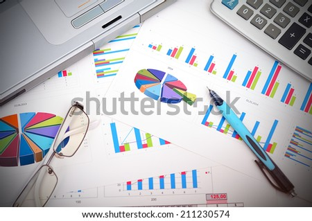 market analysis concept with financial report, pen, laptop and glasses - stock photo