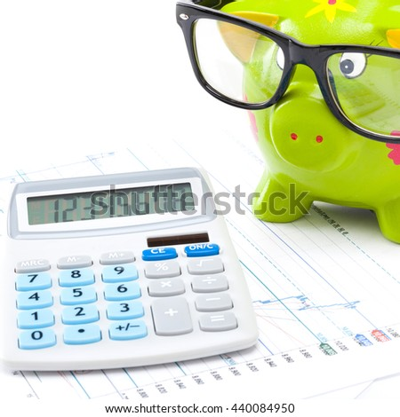 Market charts with a calculator and a piggy bank over it - stock photo