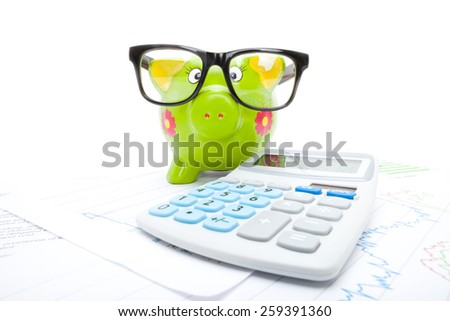 Market charts with piggy bank and calculator over it - studio shot - stock photo