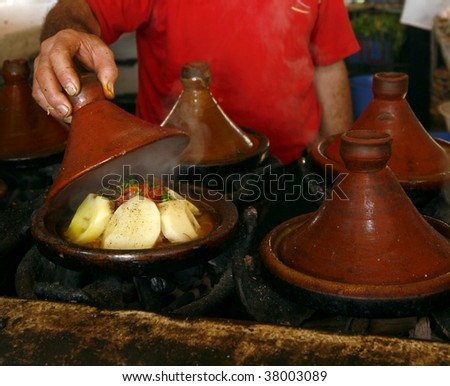 Market cook holding a cover of a tajine dish (traditional casserole). His hands are rather dirty. Marrakech, Morocco - stock photo