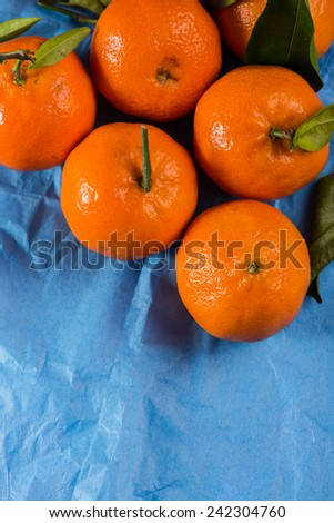 Market fresh ripe mandarins with leaves on blue background