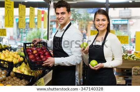 Market workers with assortment of tasty apples, prices on Spanish