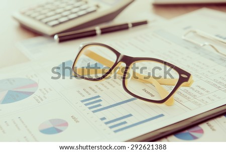 Marketer's desk with analysis Report ,Calculator, glasses. - stock photo