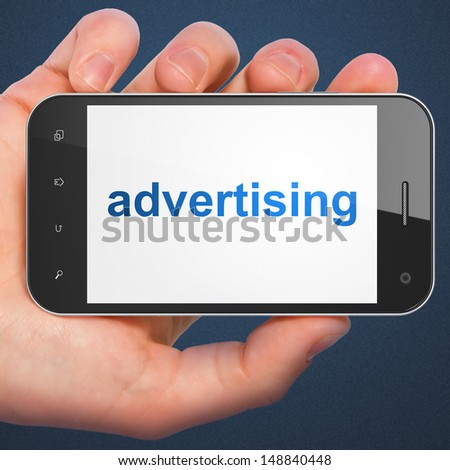 Marketing concept: hand holding smartphone with word Advertising on display. Generic mobile smart phone in hand on Dark Blue background. - stock photo