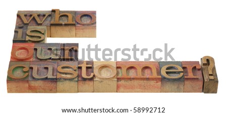 marketing concept - who is our customer question in vintage wooden letterpress printing blocks, stained by color inks - stock photo