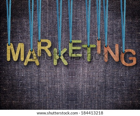 Marketing Letters hanging strings with blue sackcloth background. - stock photo