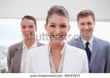 Marketing manager standing with her team behind her - stock photo