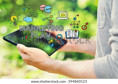 Marketing Plan concept with young man holding his tablet computer outside in the park
