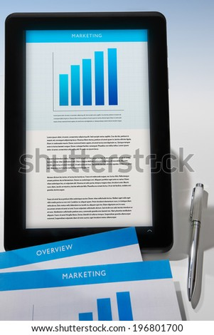 Marketing proposal on a tablet screen with printed documents and pen. - stock photo