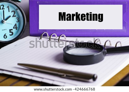 Marketing - Purple Office Folder on Background of Working Table with Magnifying glass,  a pen and clock - business and finance concept