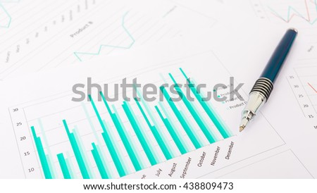 Marketing report chart and graph analysis with pen,Green graph analysis with ball pen.