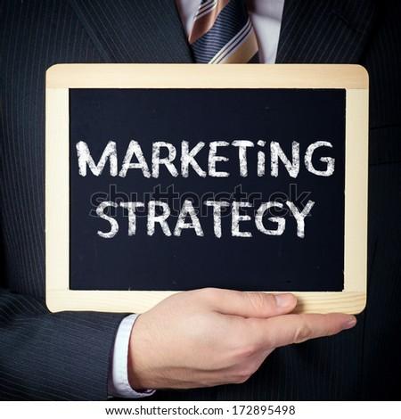Marketing Strategy handwritten on blackboard which holding man - stock photo