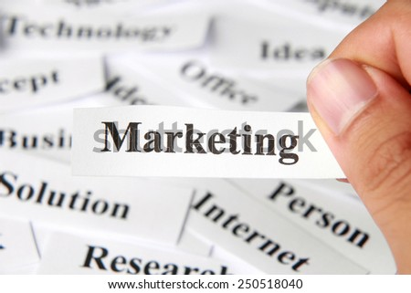 Marketing word paper in hand with the background of other words. - stock photo