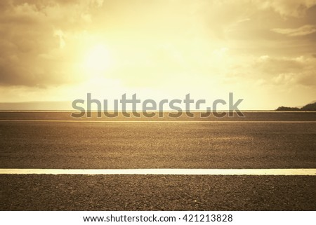 Marking line on asphalt road with sunlight from sky - stock photo