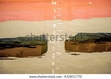 Marking the draft reflected in the harbor water - stock photo