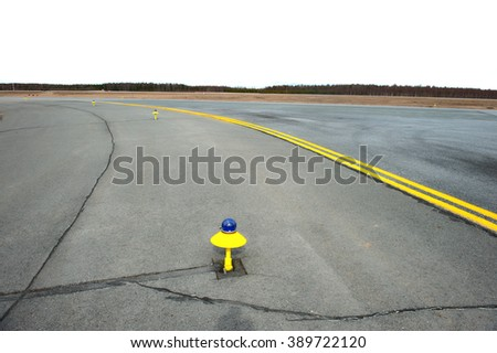 Marking yellow runway of a small airfield. In the foreground, the yellow-blue lights. - stock photo