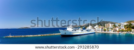 Marmari port with anchored ship and white houses against a blue sky and blue waters in Evia, Greece