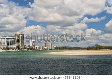 Maroochydore from Maroochy river. Sandy riverbank on opposite side and green water. Some highrise building on the other side of river and mountains on the horizon. Scattered white clouds with blue sky