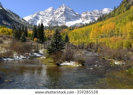 Maroon Bells and Creek in Autumn - Horizontal - An autumn morning after an overnight snowfall,  Maroon Creek, filled with crystal-clear stream, running down from Maroon Bells, Aspen, Colorado, USA. - stock photo