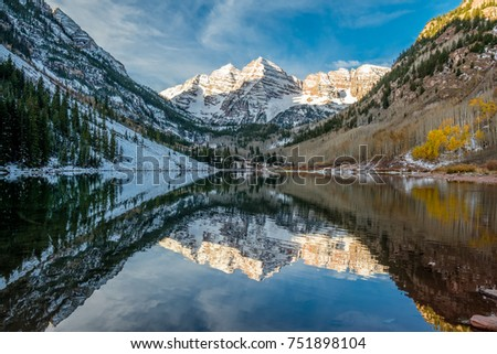 Maroon Bells and Maroon Lake with reflection of rocks and mountains in snow around at autumn in Colorado, USA.