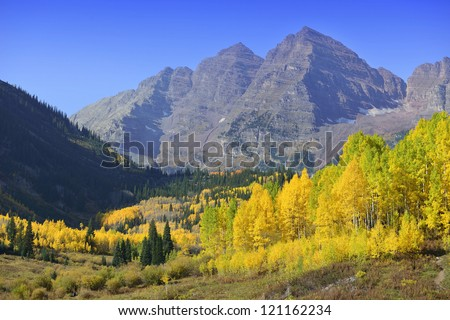 Maroon Bells, Elk Mountains, and lake with golden and green aspen during foliage season in Colorado - stock photo