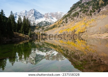 Maroon Bells mountains, with lake and reflection and green pines and yellow aspens, Aspen, Colorado, USA - stock photo