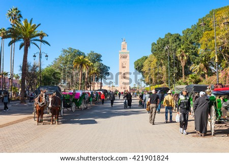 MARRAKECH, MOROCCO - FEBRUARY 22, 2016: Horse carriage and outoubia Mosque at Jemaa el Fna square and market place in Marrakesh's medina quarter. - stock photo