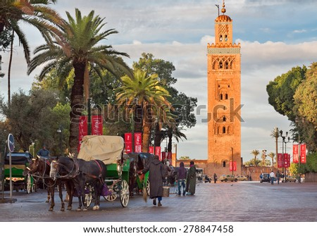 MARRAKECH, MOROCCO - NOVEMBER 30: Cab drivers in horse-drawn carriages around Koutoubia mosque awaiting tourists in Marrakech, Morocco, November 30, 2014. Marrakech popular place among tourists. - stock photo