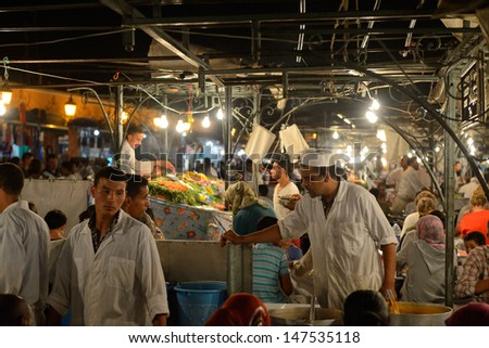 MARRAKESH - JULY 09: Unidentified people sells food in Jemaa el Fna Square at sunset, July 09, 2013 in a Marrakesh, Morocco. The square is part of the UNESCO World Heritage - stock photo