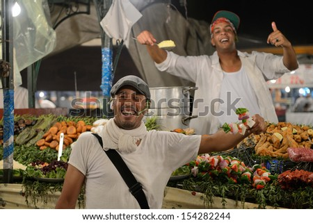 MARRAKESH - JULY 10: Unidentified people sells food in Jemaa el Fna Square at sunset, July 10, 2013 in a Marrakesh, Morocco. The square is part of the UNESCO World Heritage - stock photo