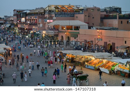 MARRAKESH - JULY 09: Unidentified people visit the Jemaa el Fna Square at sunset, July 09, 2013 in a Marrakesh, Morocco. The square is part of the UNESCO World Heritage. - stock photo