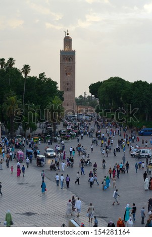 MARRAKESH - JULY 09: Unidentified people visit the Jemaa el Fna Square near Koutoubia Mosque, July 09, 2013 in a Marrakesh, Morocco. The square is part of the UNESCO World Heritage. - stock photo