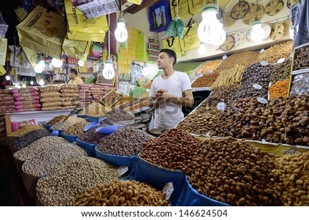 MARRAKESH - JULY 09: Unknown man trades a dried fruits in a market (souk), July 09, 2013 in a Marrakesh, Morocco. The market is one of the most important attractions of the city Marrakesh, Morocco - stock photo
