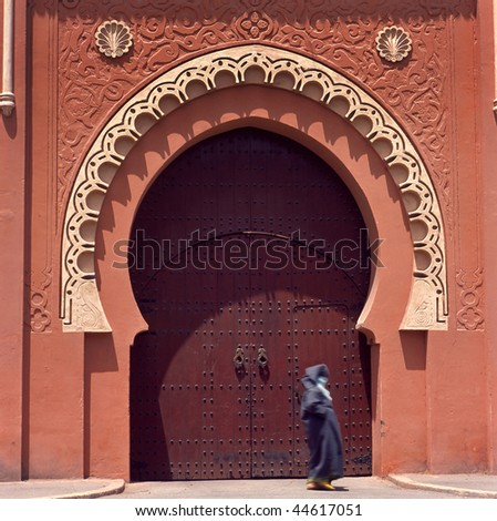 Marrakesh medina decorated gate.Lady is not recognizable because of total veil.