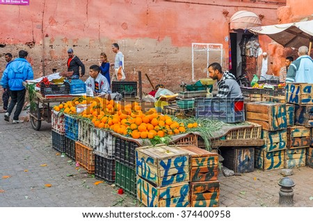 MARRAKESH, MOROCCO, APRIL 3, 2015:  Local sellers offer oranges and other fruits on street stands in souks - stock photo