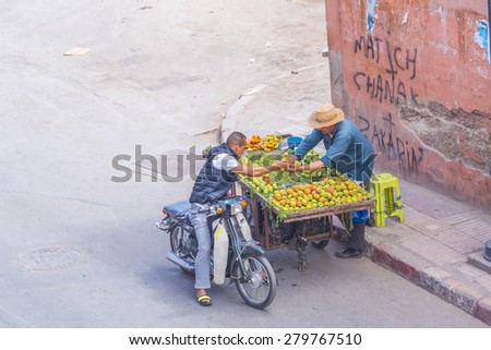 MARRAKESH, MOROCCO, APRIL 3, 2015: Vendor of  opuntia fruits offers his merchandise on street - stock photo