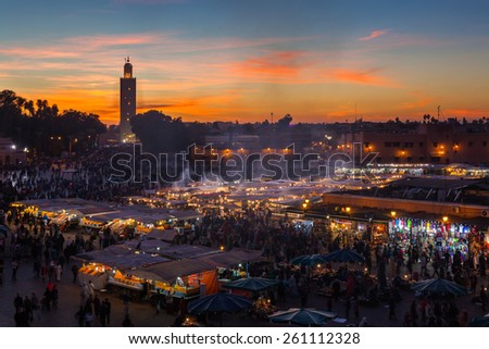 MARRAKESH, MOROCCO - DECEMBER 27: Crowd in Jemaa el Fna square at sunset on December 27, 2014 in Marrakesh, Morocco. Blur of moving objects and people to imply movement. - stock photo