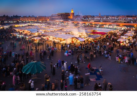 MARRAKESH, MOROCCO - DECEMBER 28: Crowd in Jemaa el Fna square at twilight, on December 28, 2014 in Marrakesh, Morocco. People blur to imply their movements. - stock photo