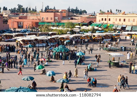 MARRAKESH, MOROCCO - JAN 27: People walking at famous Marrakesh square Djemaa el Fna on January 27, 2010 in Marrakesh, Morocco. The square is part of the UNESCO World Heritage. - stock photo