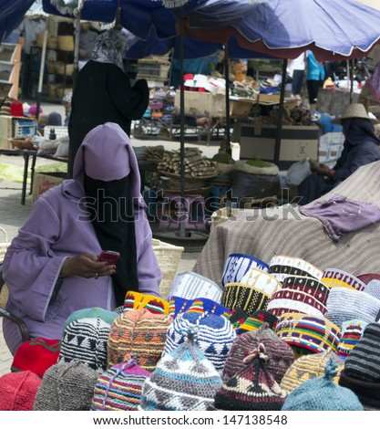 MARRAKESH ,MOROCCO - JUNE 4: Unidentified woman selling hats at a street in Marrakesh medina on June 4, 2013 in Morocco. In 2009 the medina got part of UNESCO World Heritage.  - stock photo