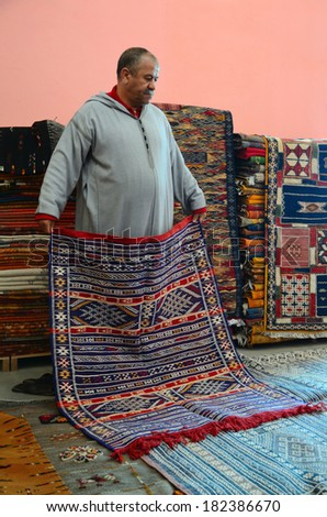 Marrakesh, Morocco - March 12, 2014: Oriental berber rugs in a carpet store in Morocco. The seller shows a carpet to buyers. - stock photo