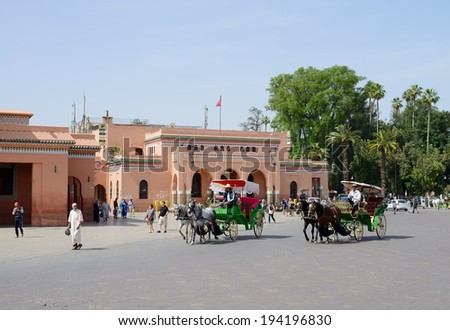 MARRAKESH, MOROCCO - MAY 9: Horse and carriages carrying customers and tourists near to landmark of mosque near market square . Marrakesh, Morocco May 9, 2014 - stock photo