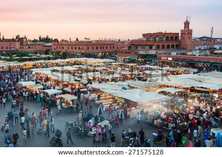 MARRAKESH, MOROCCO - MAY 25, 2014: Sunset over Jamaa el Fna - also Jemaa el Fnaa, Djema el Fna or Djemaa el Fnaa - square and market place in medina quarter. During the night its full of food stalls - stock photo