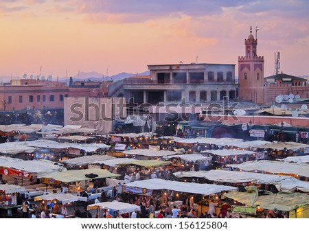 MARRAKESH, MOROCCO - MAY 03: Unidentified crowd on the Jemaa el Fna Square during the sunset on May 03, 2013 in a Marrakesh, Morocco. The square is declared UNESCO World Heritage Site. - stock photo